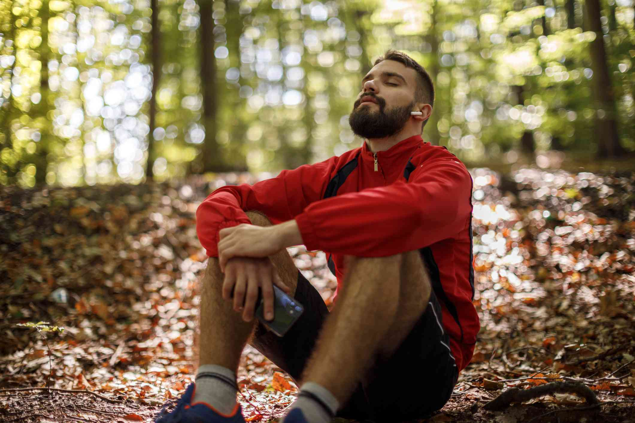 A white man with a beard sits in the forest and breathes the fresh air.