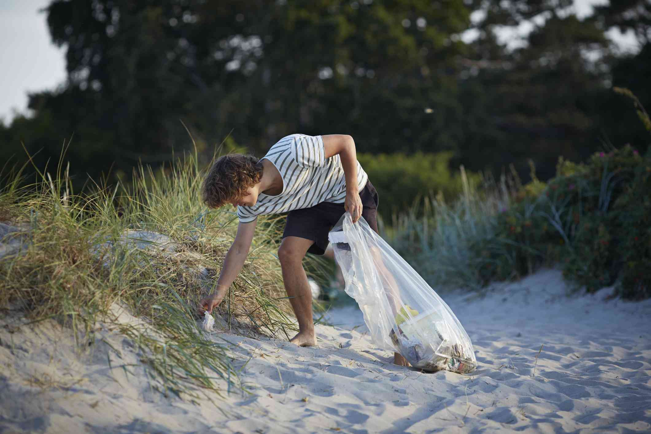 A teenager picking up garbage on the beach.