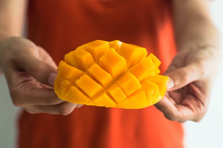 A woman in an orange dress holds a slice mango.