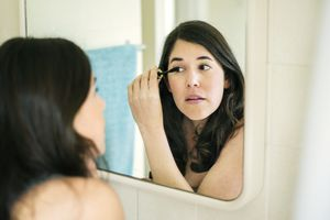 A brunette woman applies mascara to her eyes in the mirror.
