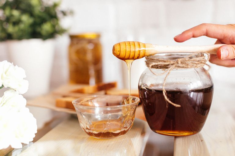 Honey from a glass jar slowly pouring into a glass bowl.