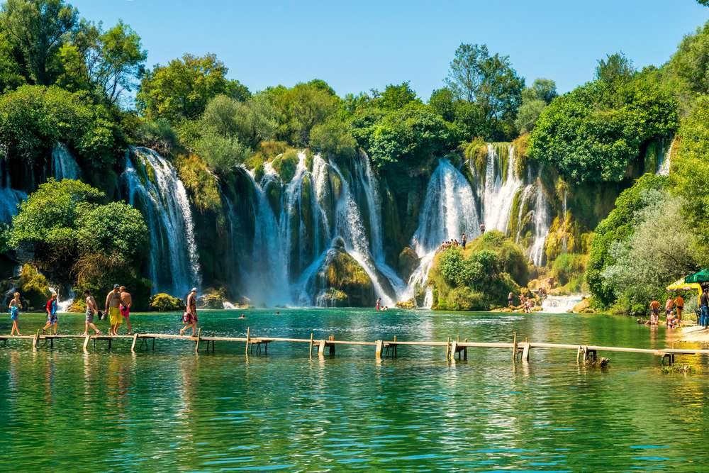 The cascading Kravice Falls flow into a pool with a boardwalk across it