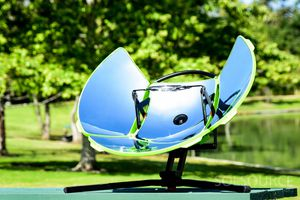 One Earth Designs' solar cooker outdoors with trees and grass in the background