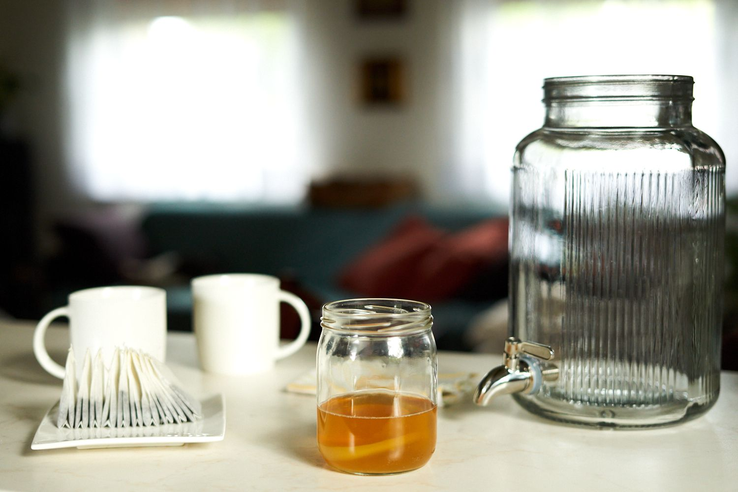 gallon-size glass container and kombucha-making supplies displayed in home