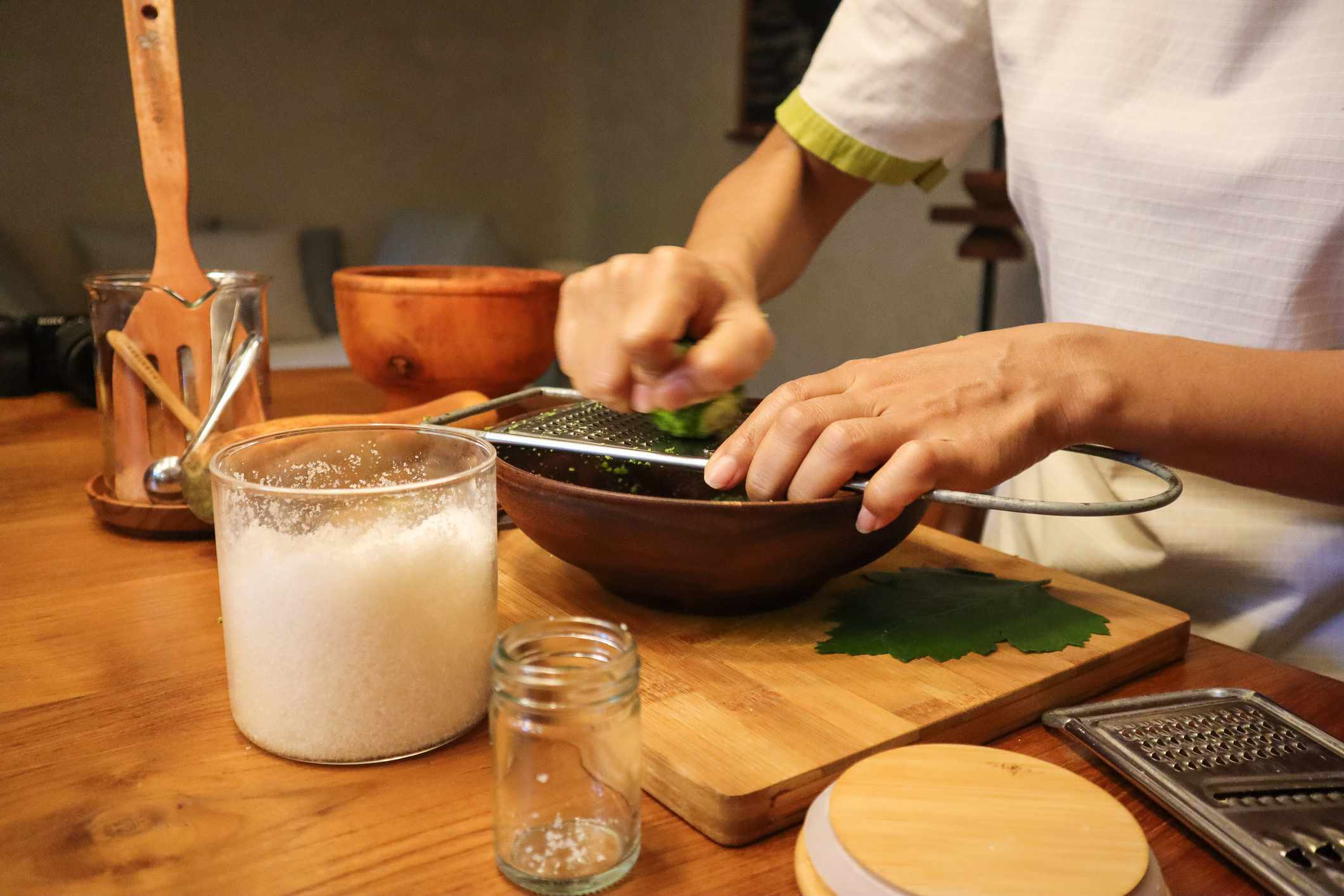 Woman zesting a lime surrounded by salt scrub ingredients