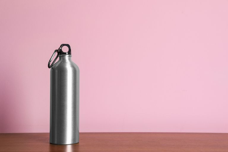 Silver metal water bottle on a table in front of a pink wall