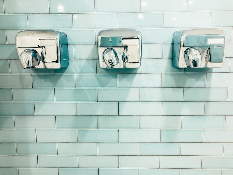 Three silver hand dryers on a teal tile wall
