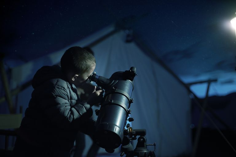 Boy looking through telescope at night