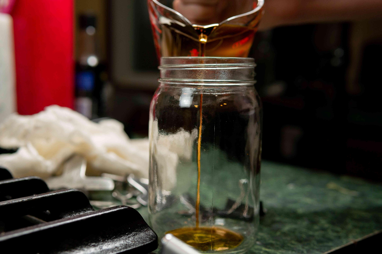 pouring boiled sugar water into clean mason jar