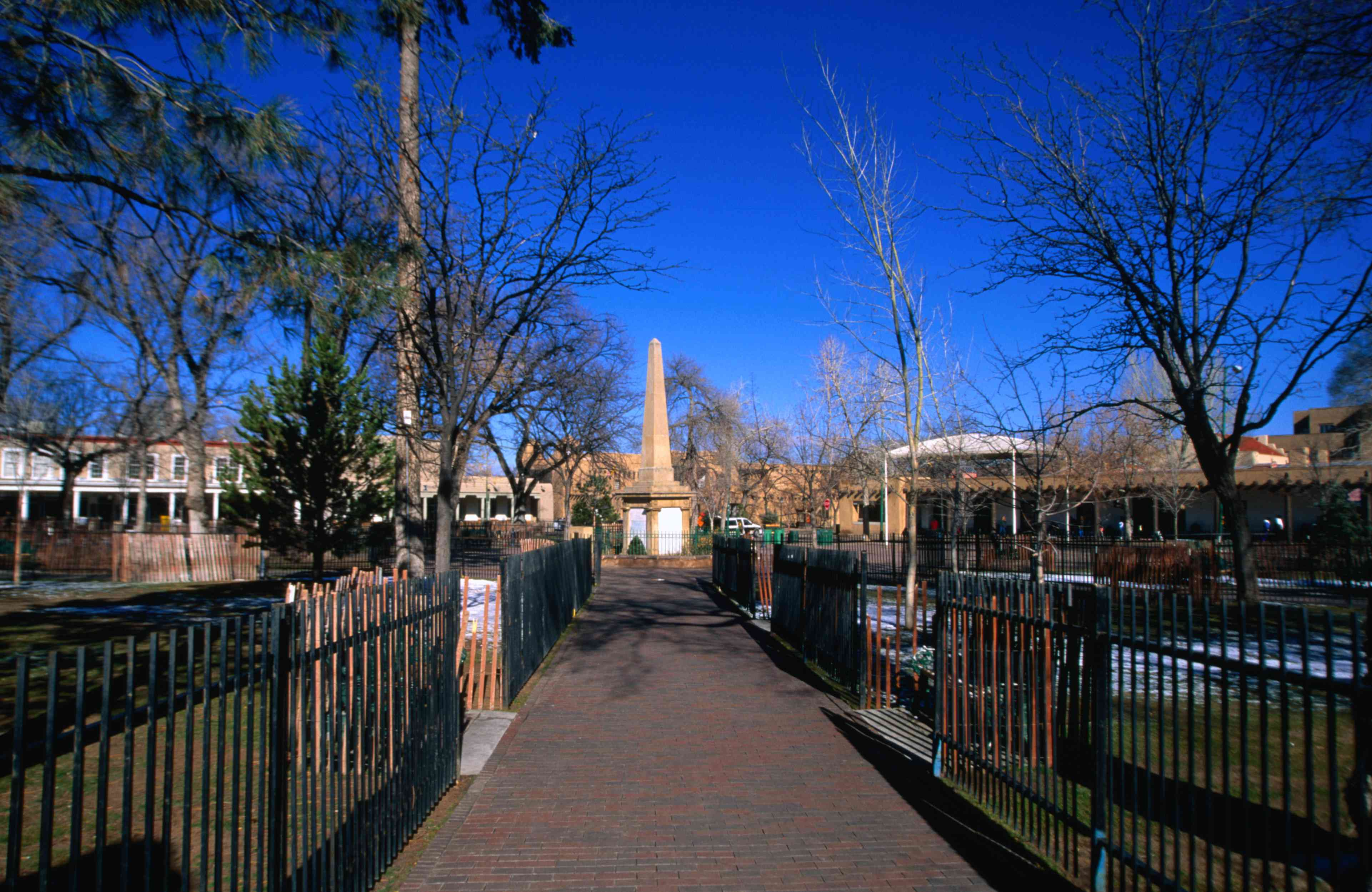 Trees and grass behind a black iron fence lining a brick pedestrian path leading to a plaza in downtown New Mexico under a vivid blue sky on a sunny day