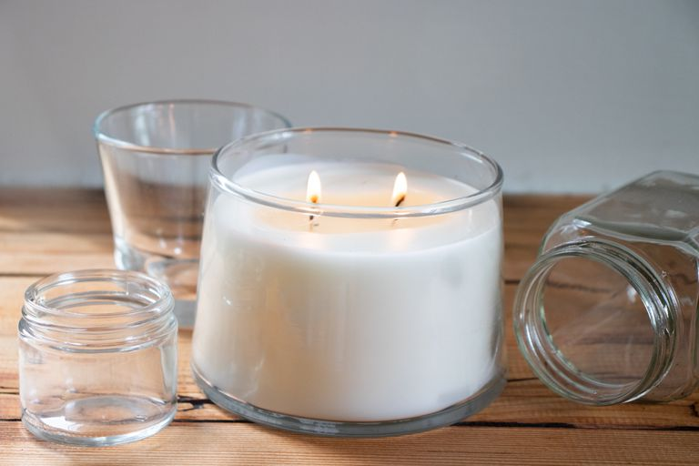 lit white candle on wooden table surrounded by empty glass candle jars