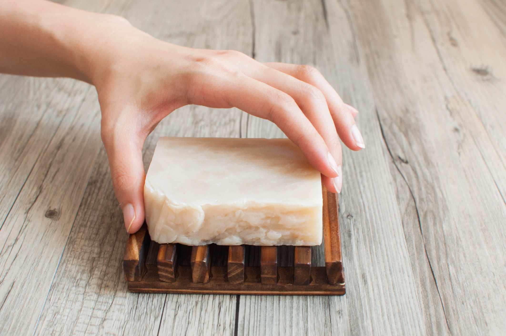 Hand reaching for homemade shampoo bar