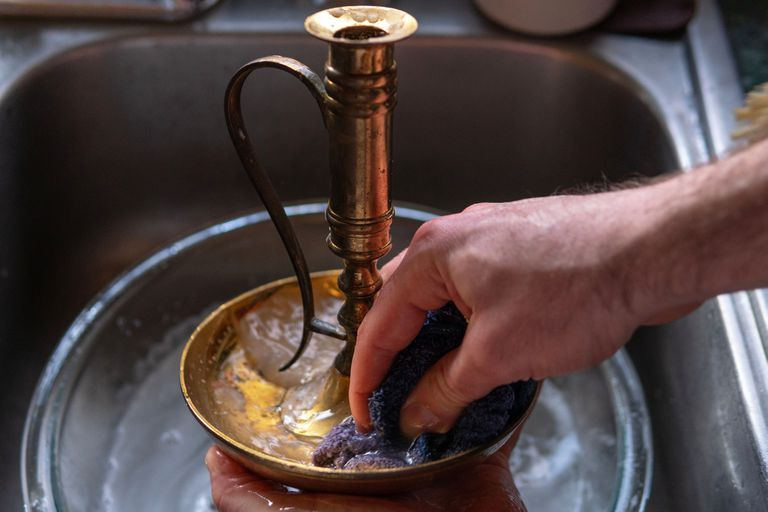 hands clean brass candlestick in sink