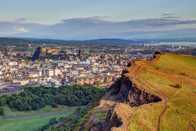 View of Edinburgh old town and castle with part of Arthur's Seat mountain visible in foreground, green grass and lush trees below, and blue sky above