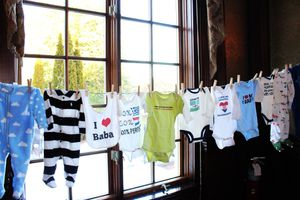 baby bibs and onesies drying on a clothes line in front of a window