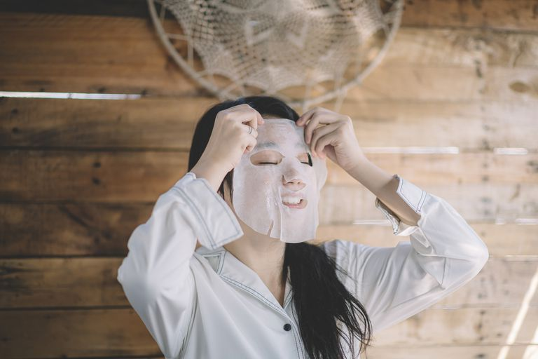 An Asian woman puts a face mask on in a rustic cabin.