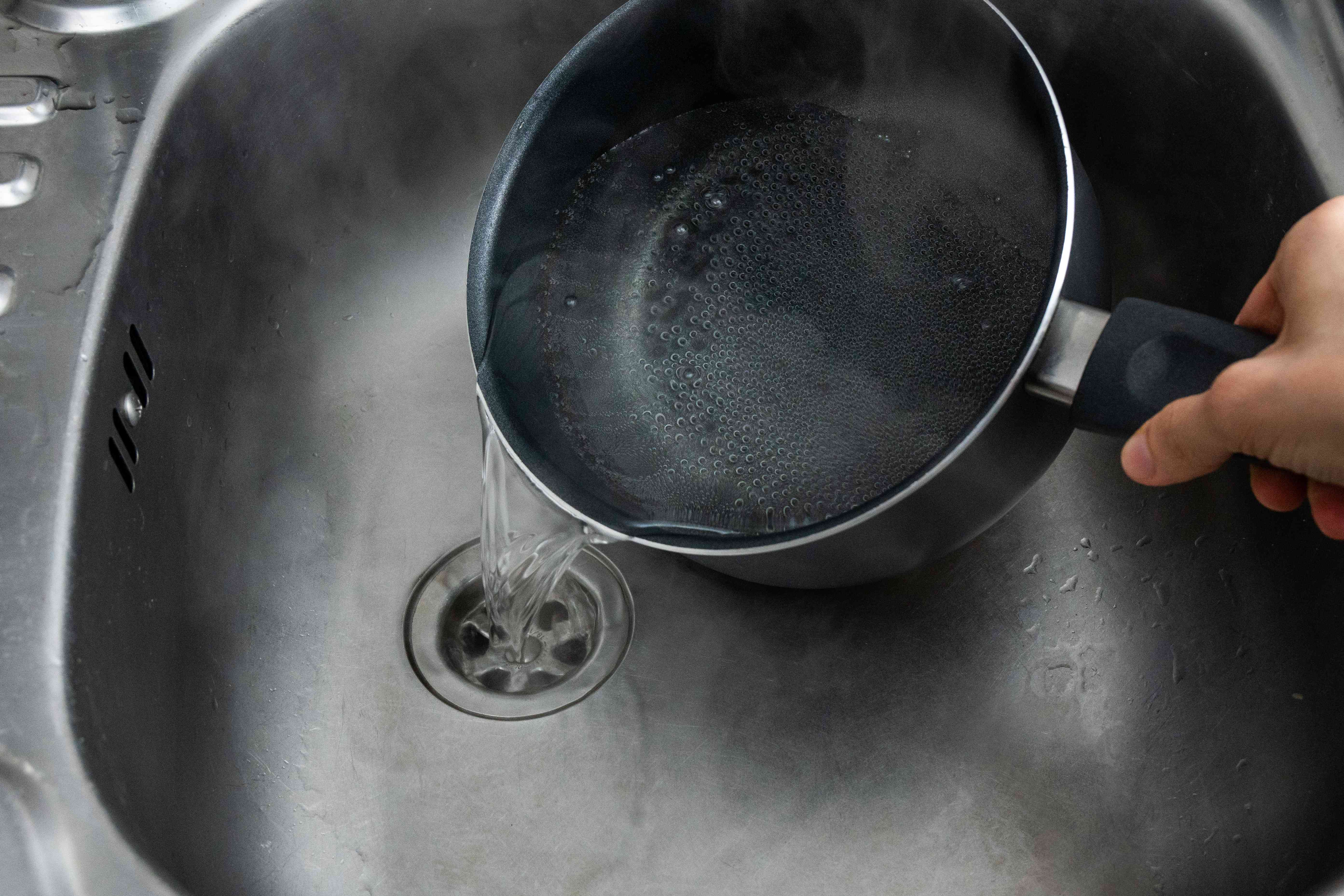 hand pours boiling water down stainless steel sink