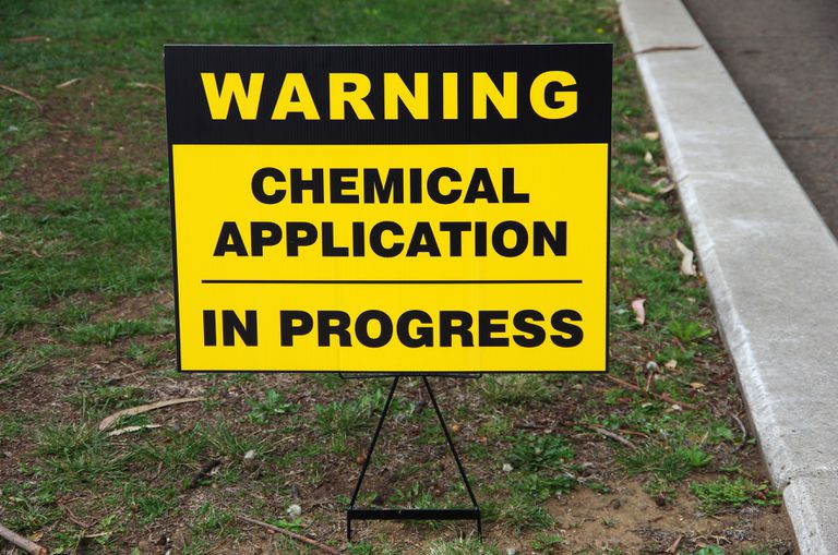 Warning: Chemical application in progress' sign in a lawn