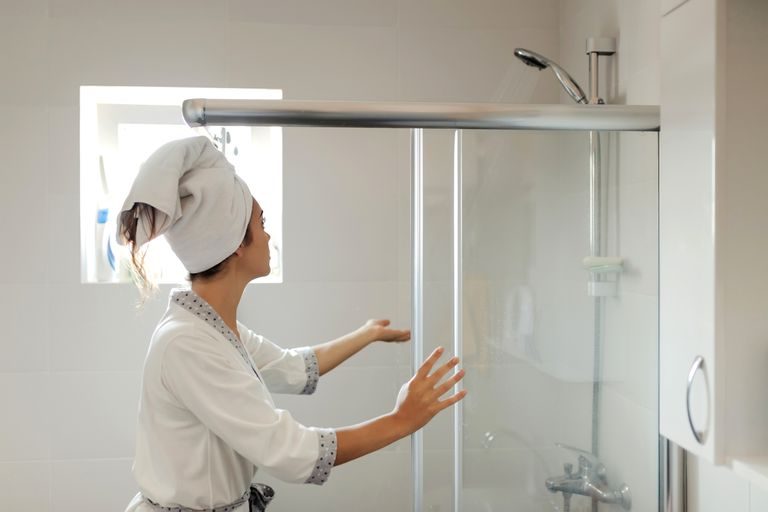 A woman in a towel and robe puts her hand in the shower to test water.