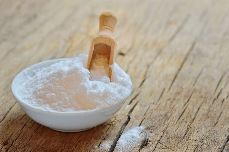 baking soda in a bowl with a wooden scoop
