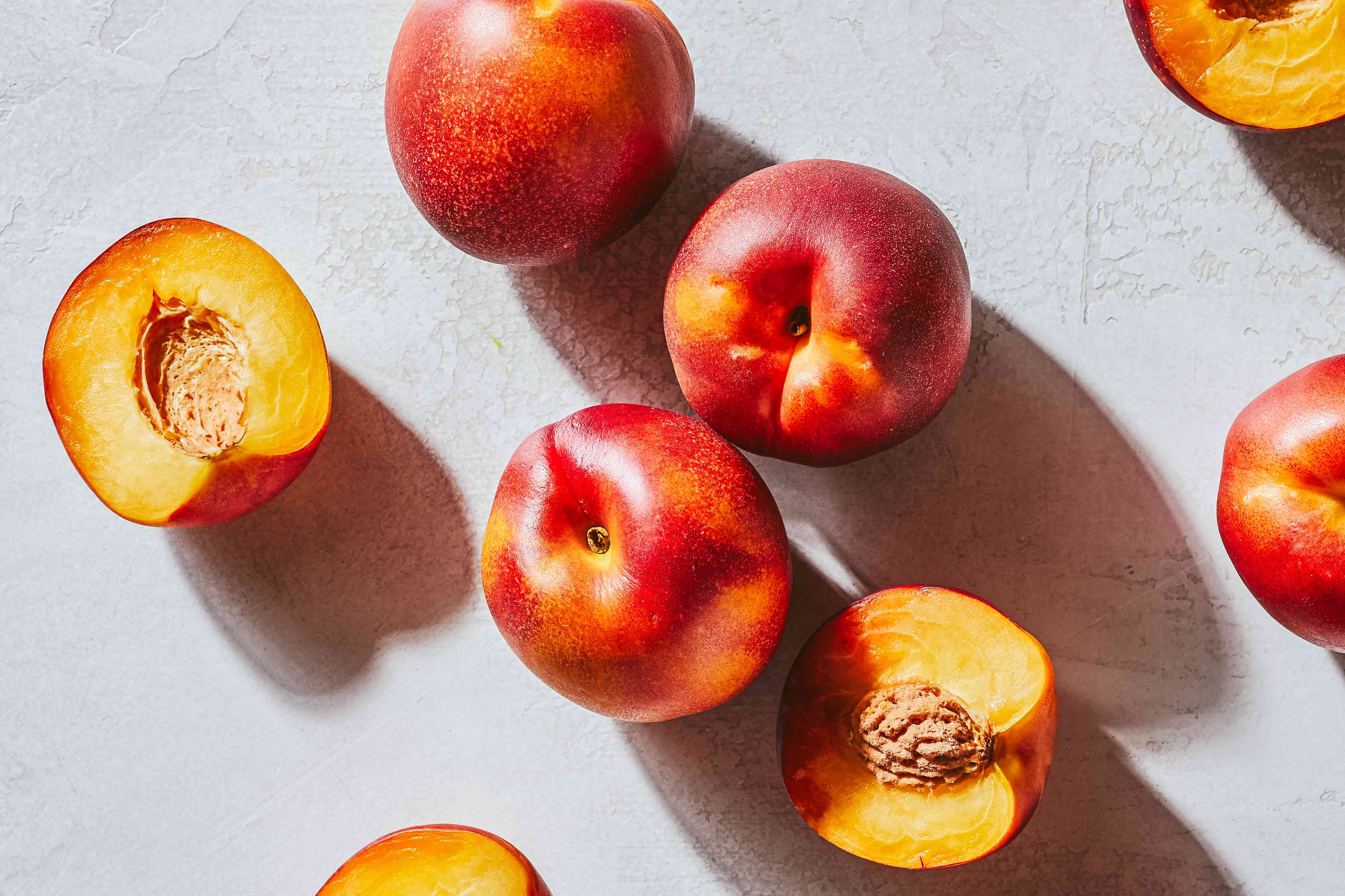 cut and whole nectarines with seed shown scattered on textured white surface