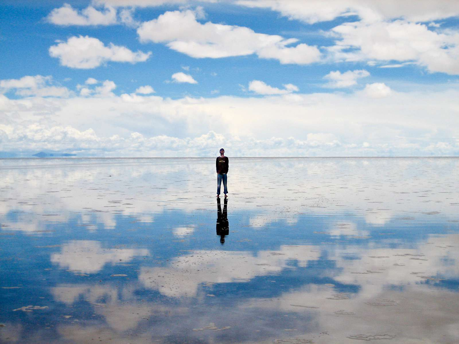 A man looks up into the sky while standing on the Salar de Uyuni while the sky is reflected on the ground