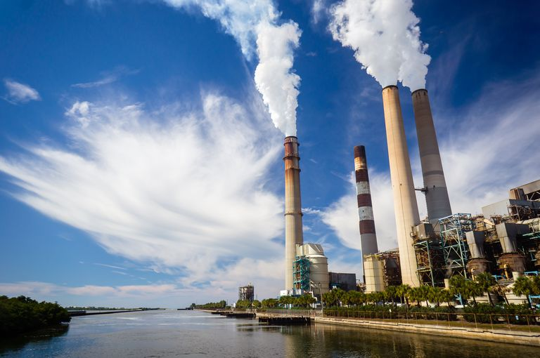 A power plant polluting the air and water it is built beside.
