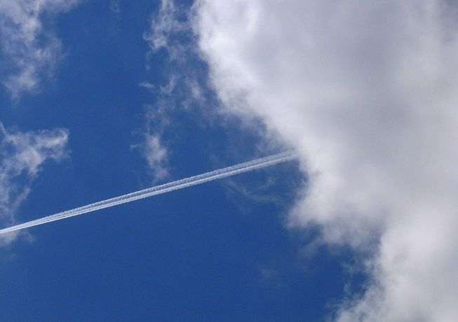 A contrail streaks out of some clouds
