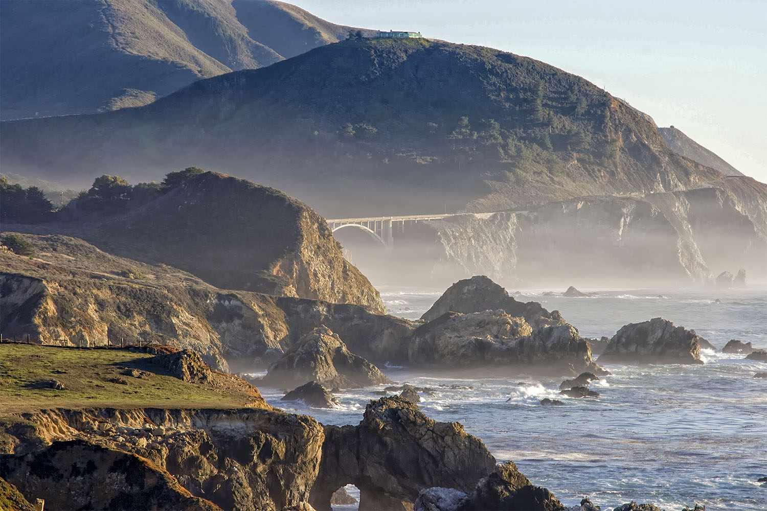 The misty and rocky coast of Big Sur on a partially cloudy day in California