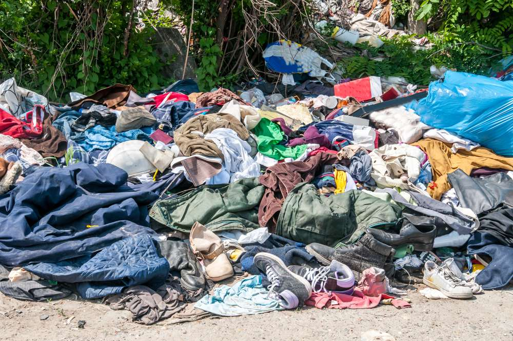 Pile of old clothes and shoes dumped on the grass as junk and garbage