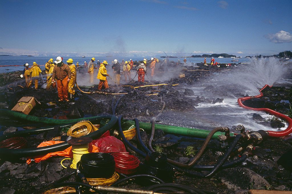 Firefighters spray water from firehoses to clean up oil from shorelines