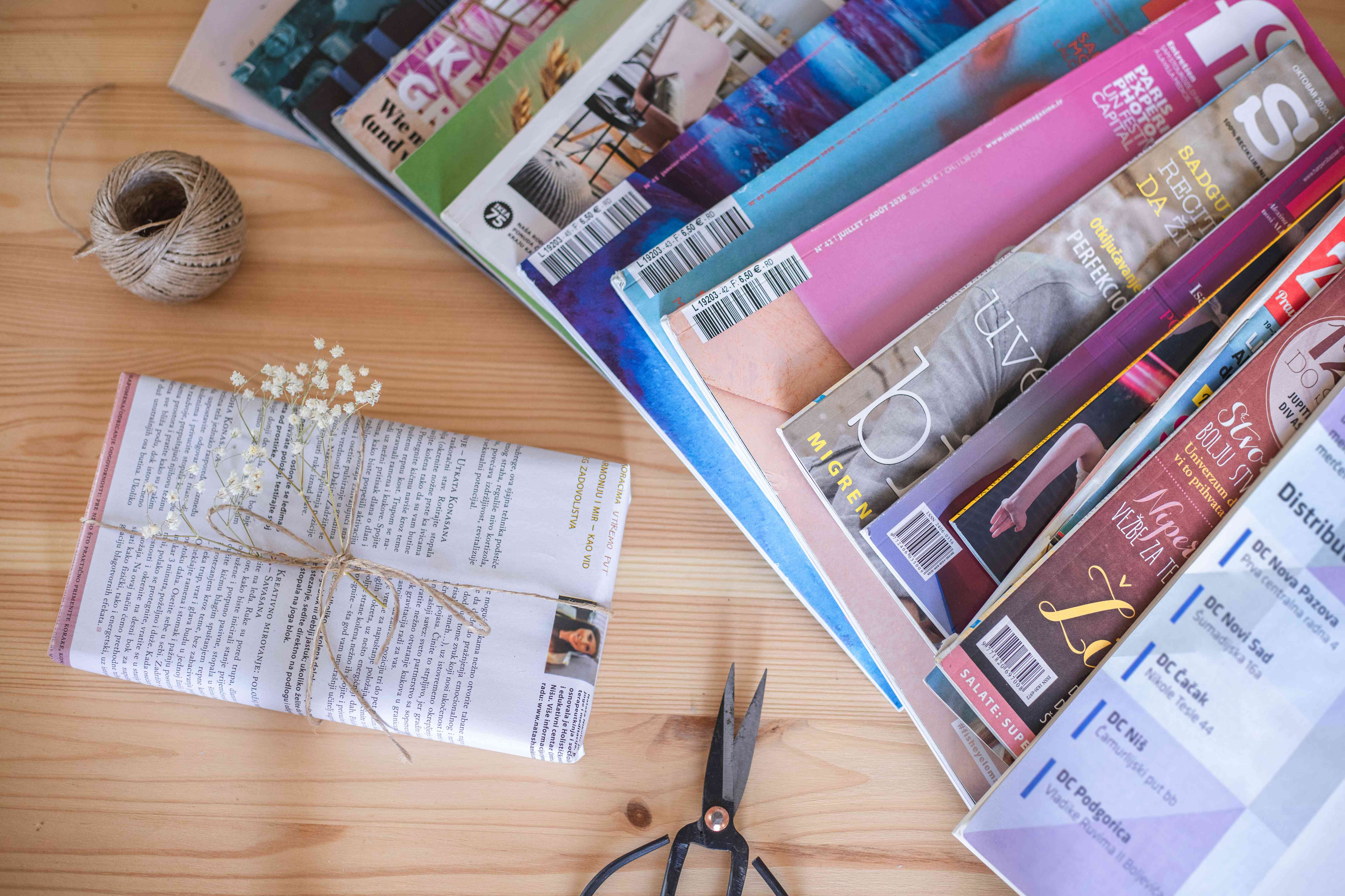 magazines scattered on table next to scissors, twine, and gift-wrapped present in upcycled paper
