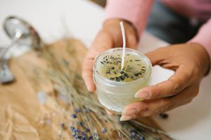 hands hold diy soy candle with lavender
