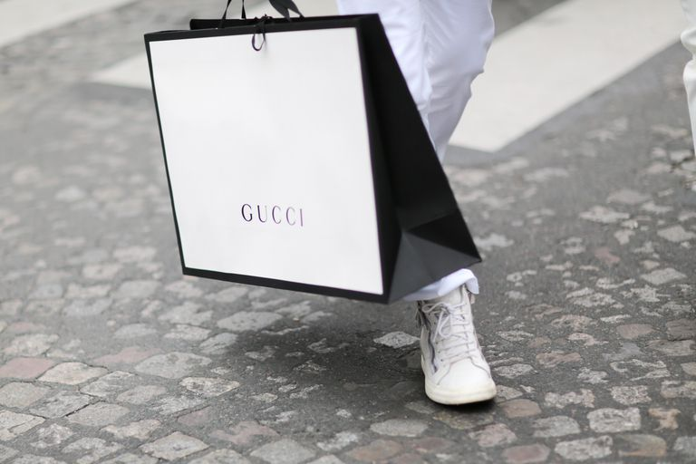 A Gucci shopping bag being carried on a cobbled street.