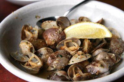 Bowl of clam tapas with a lemon wedge on top