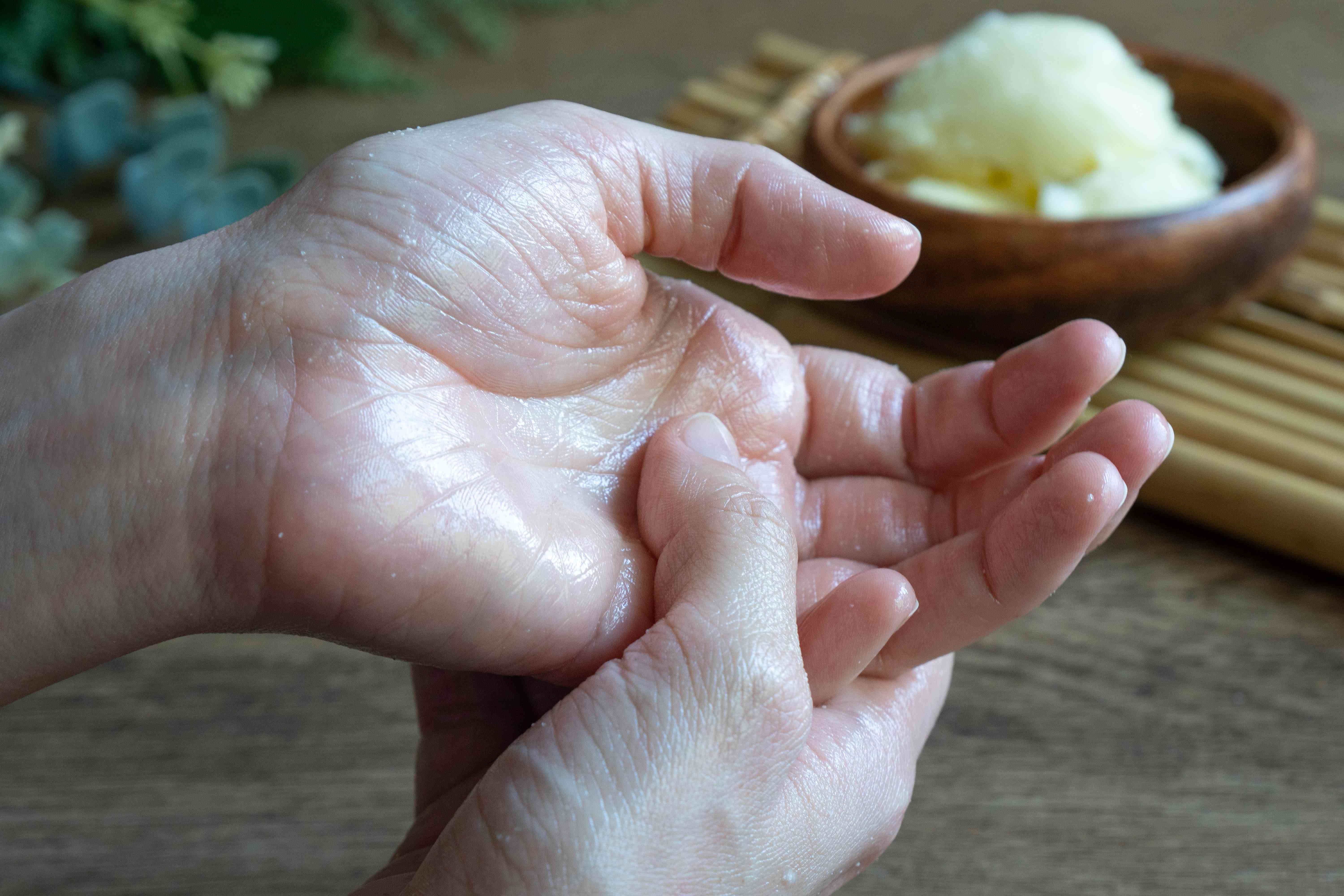 two hands rub shea butter into palm, with wooden bowl of raw shea butter in background