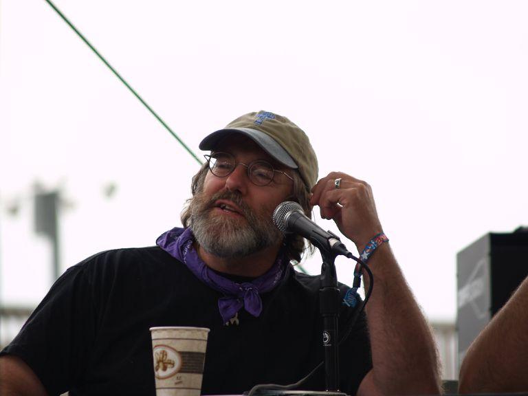 Mushroom expert Paul Stamets speaking at an event outdoors.