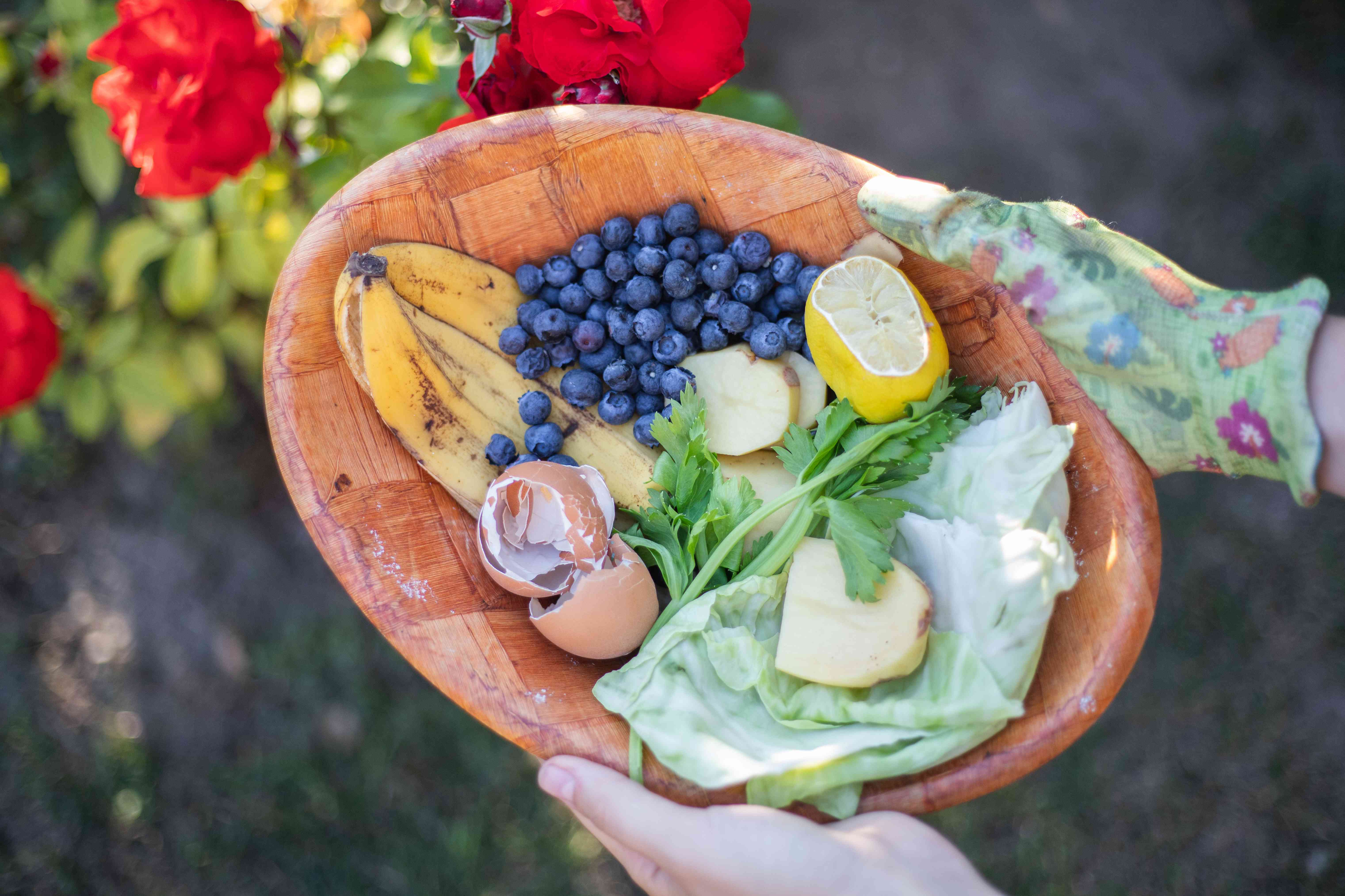 person carries wooden bowl full of food scraps outside to compost pile