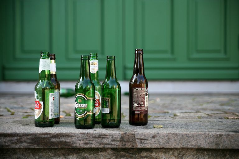 empty beer bottles sit in a group on a porch