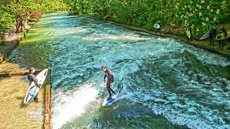 Surfers riding waves on a narrow waterway