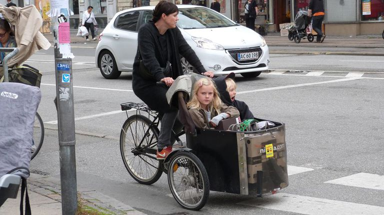 Street scene showing a woman riding a bike with two children in a front basket