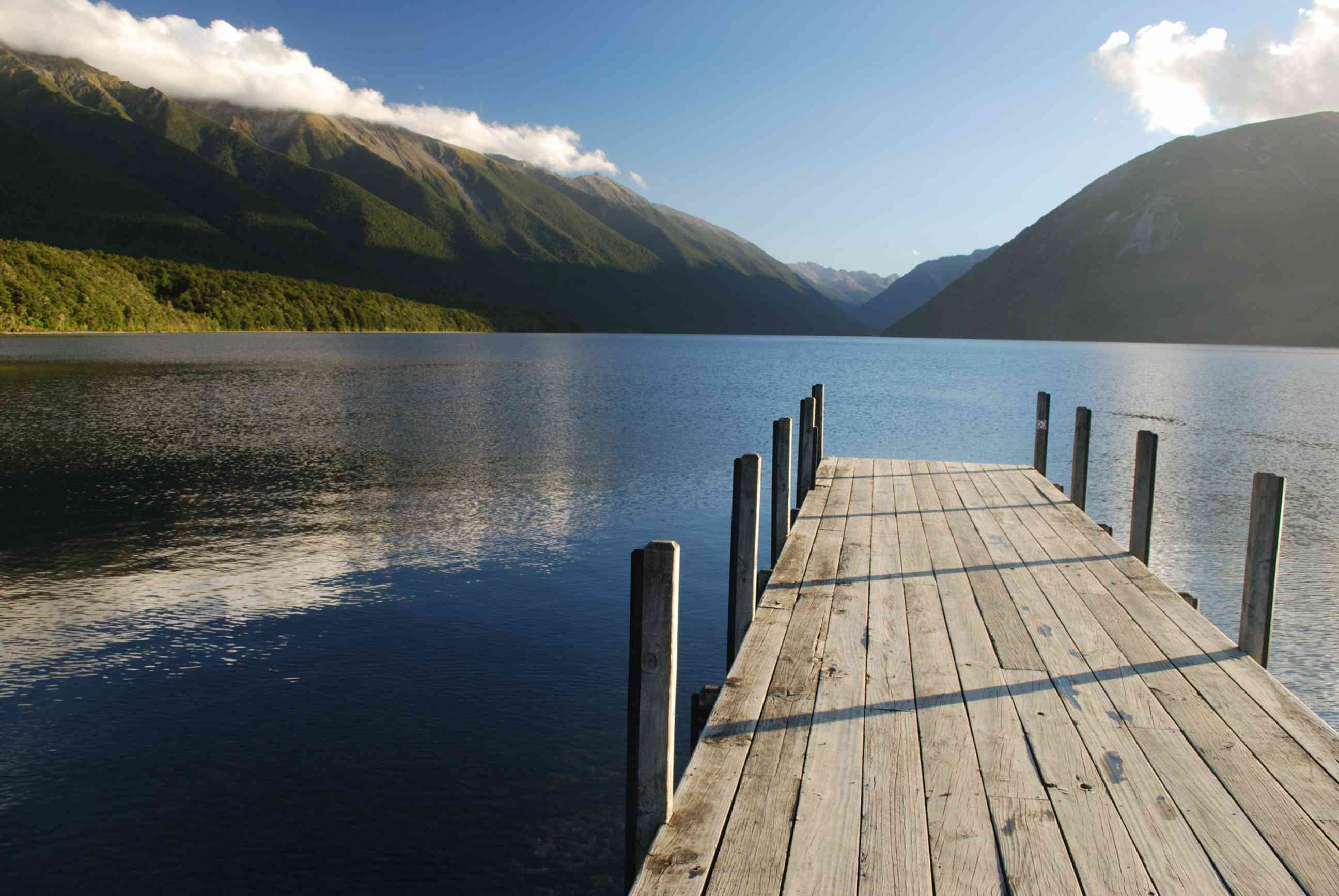 A wooden jetty on Lake Rotoiti in Nelson Lake National Park with lush, green mountains in the distance