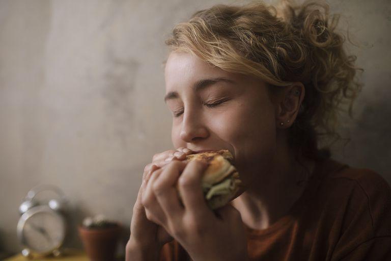 blonde girl eating a sandwich burger