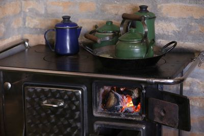 Wood burning stove with kettles and pots on top of it.