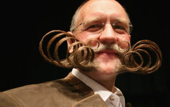 Thinly curled moustache and beard