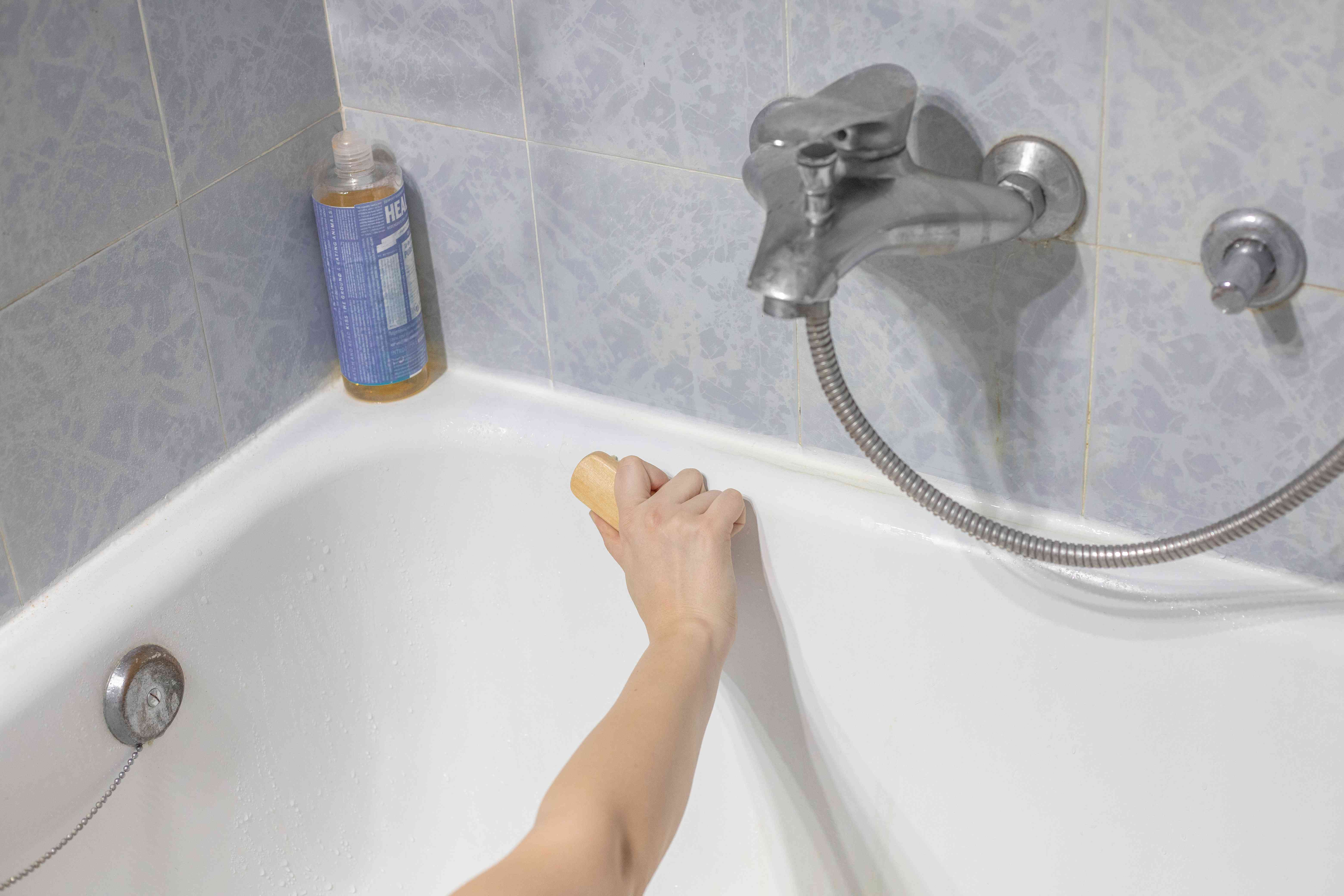 hands scrub shower tub with dr bronners bottle