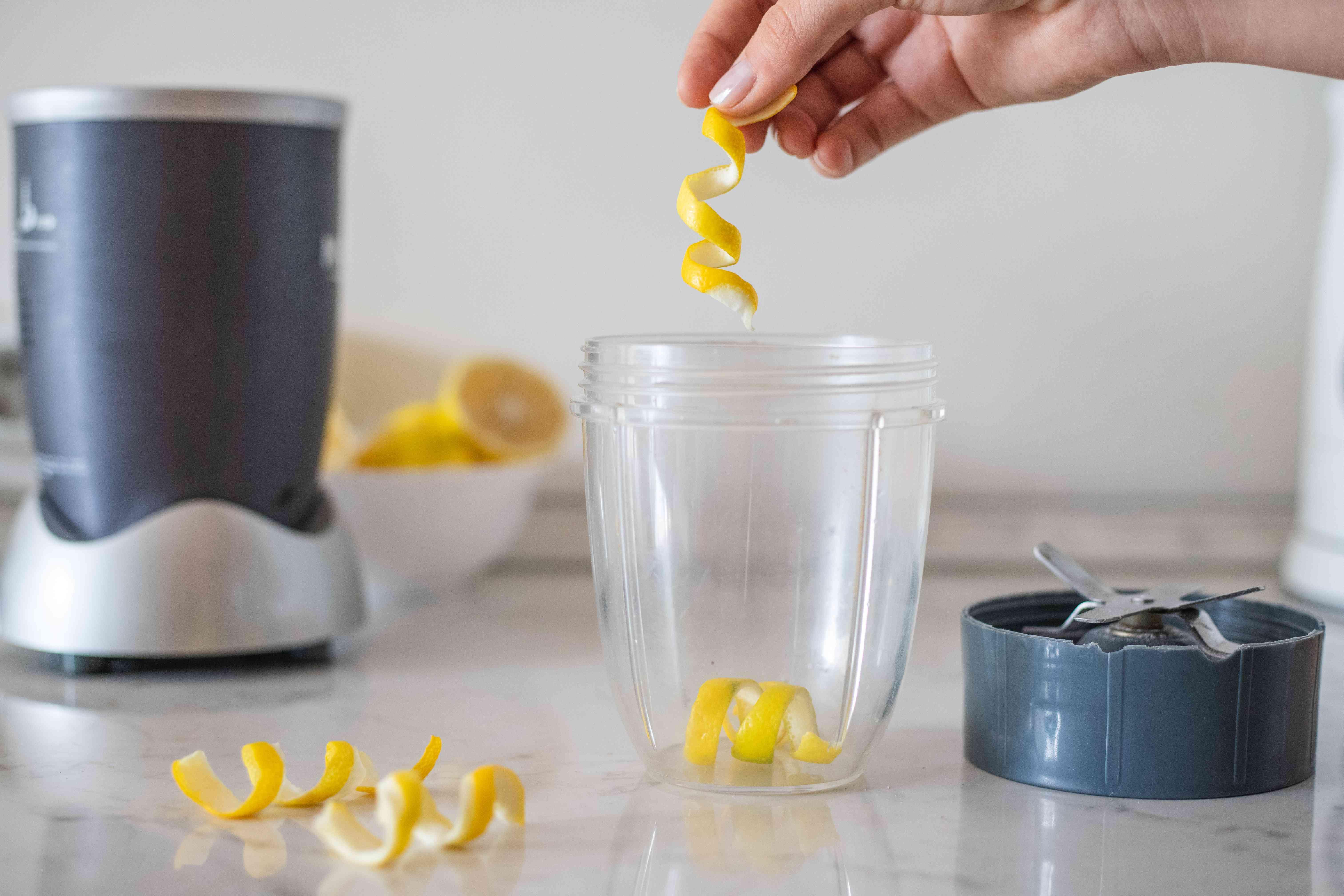 hand drops lemon peel into small blender to pulverize into citrus zest