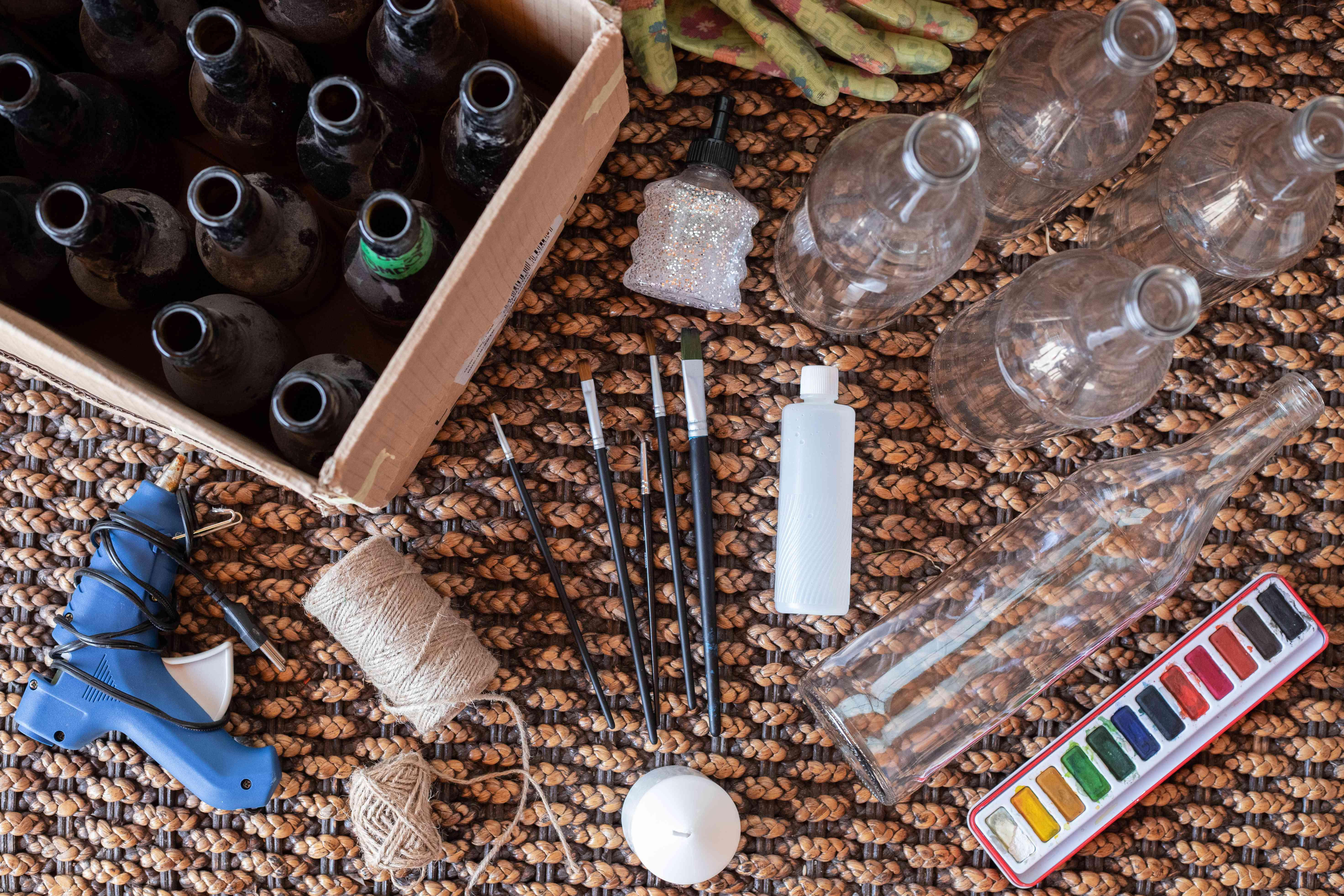 flat lay shot of glass bottles to be upcycled in crafts project with supplies and paint