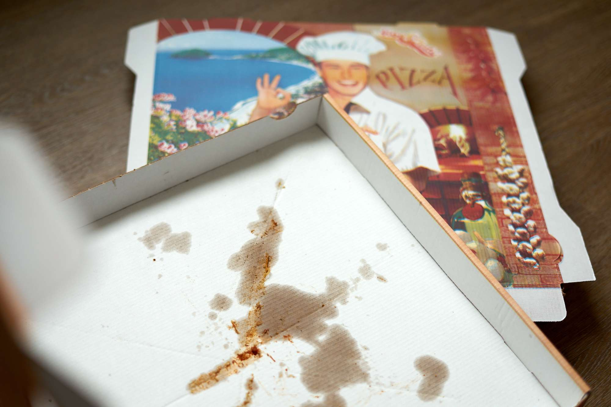 opened oily pizza box on top of closed pizza box with chef branding