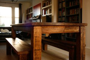 Farmhouse table built with sustainable wood with bookshelves in the background